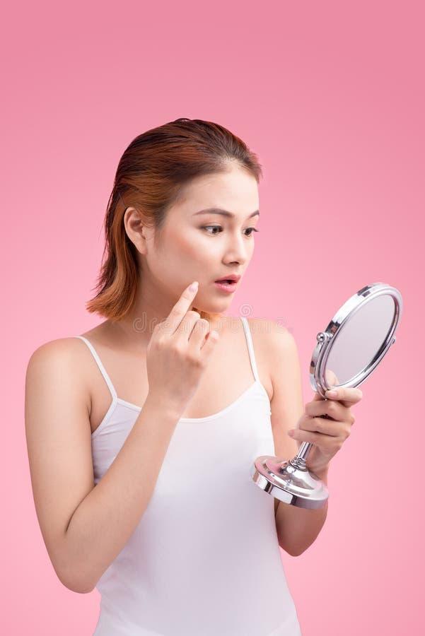 Mulher asiática consideravelmente nova que guarda um espelho, toque e preocupando o ab imagem de stock