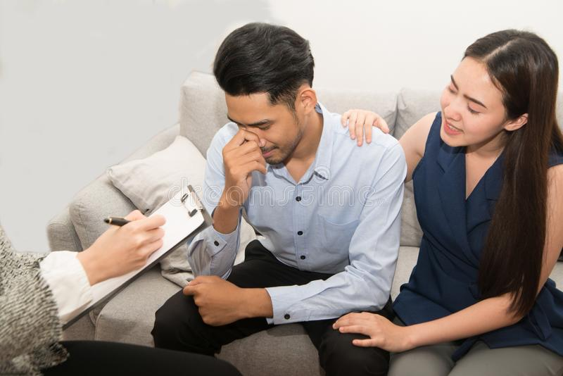 Mulher asiática consolando seu marido sentado no sofá com psicóloga foto de stock
