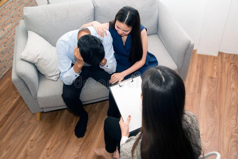 Mulher asiática consolando seu marido sentado no sofá com psicóloga imagem de stock