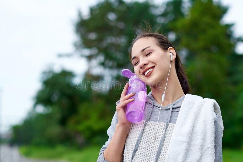 Mulher asiática da aptidão com garrafa e toalha da água após ter corrido o treinamento no parque do verão fotografia de stock royalty free