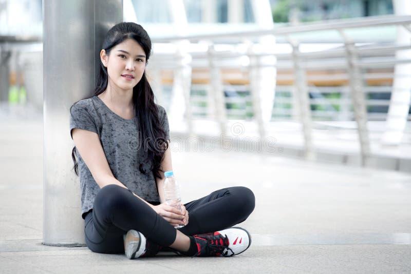 mulher asiática da aptidão que toma uma ruptura após o exercício que exercita com uma garrafa de água na rua na cidade urbana Res fotografia de stock