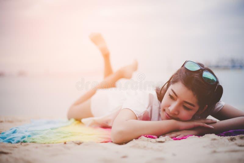 A mulher asiática da beleza tem férias na praia Óculos de sol vestindo da menina e encontro na esteira colorida perto do mar Esti fotografia de stock