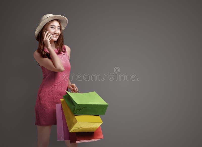 Mulher asiática da compra que fala no telefone e que guarda sacos foto de stock royalty free