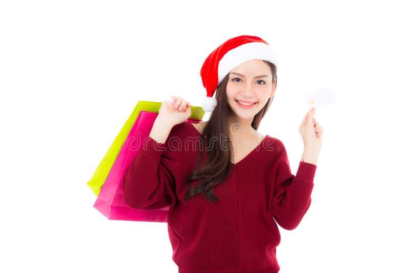 Mulher asiática da forma feliz com o sorriso que guardam o cartão de compra do saco de papel e de crédito, a venda e o Natal com  imagem de stock