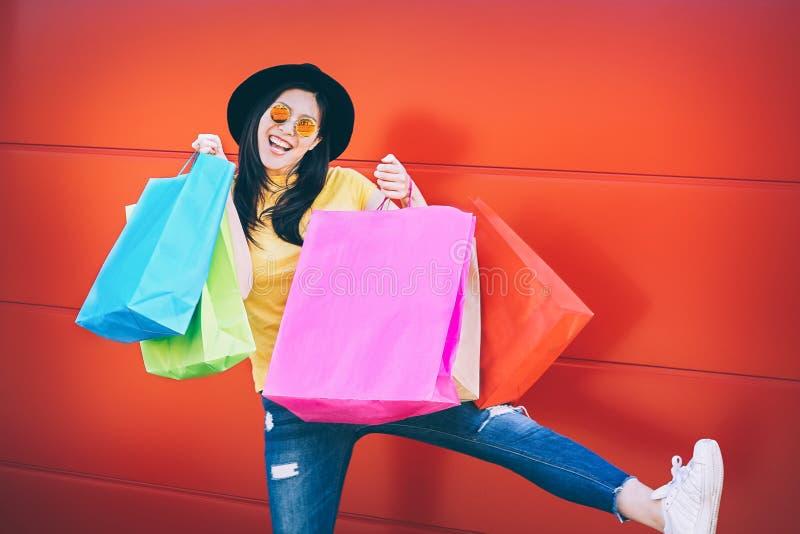 Mulher asiática da forma feliz que faz a compra no centro da alameda - menina chinesa nova que tem o divertimento que compra a ro fotos de stock