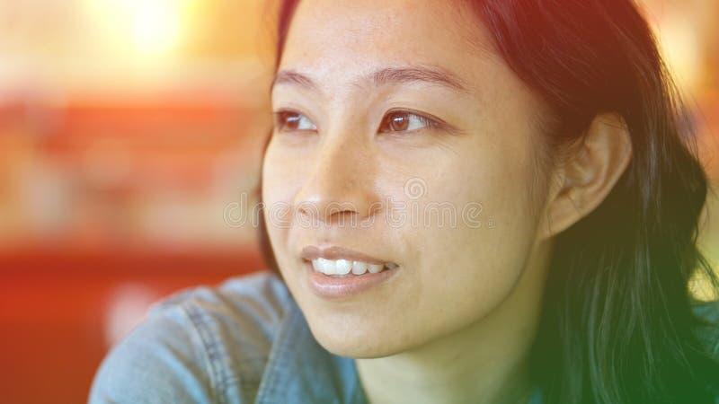 Mulher asiática da raça misturada que olha afastado, pensando e sorrindo fotos de stock royalty free