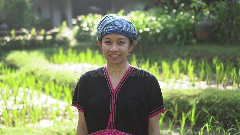 Mulher asiática das éticas com sorriso nativo do vestido em seu arroz orgânico fi fotos de stock royalty free
