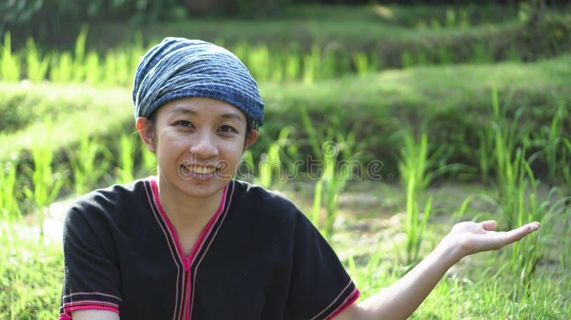 Mulher asiática das éticas com sorriso nativo do vestido em seu arroz orgânico fi imagens de stock royalty free