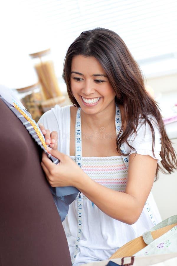 Mulher asiática de incandescência que trabalha com roupa em casa imagem de stock royalty free