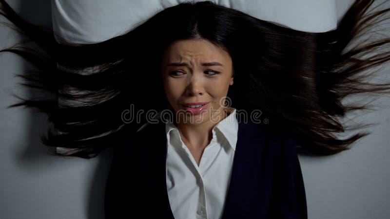 Mulher asiática de negócios estressada deitada na cama, com medo de trabalho de escritório interminável fotografia de stock royalty free