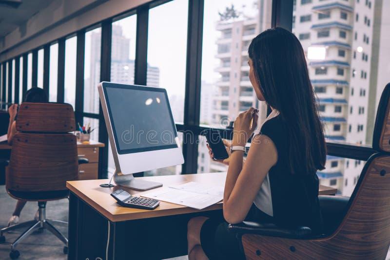 Mulher asiática de negócios sentada em sua mesa com o computador desktop no prédio moderno de escritórios imagens de stock