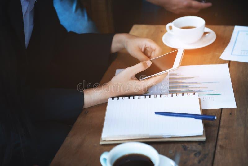 Mulher asiática de negócios usa cliente de contato de celular inteligente em reunião de grupo no café com caderno e papel de fotos de stock