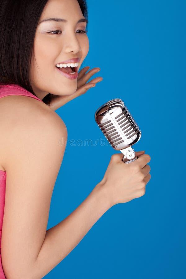 Mulher asiática de riso com um microfone imagem de stock royalty free
