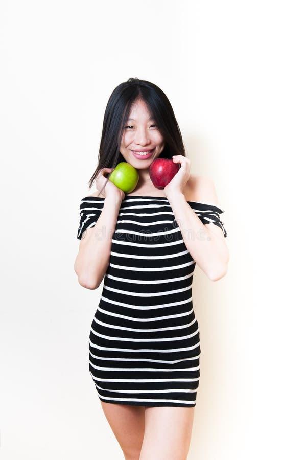 Mulher asiática de sorriso bonita nova com as maçãs verdes e vermelhas fotos de stock royalty free