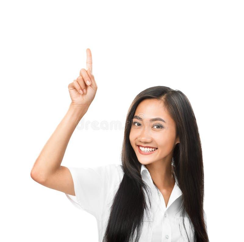 Mulher asiática de sorriso feliz que aponta acima e que olha a câmera imagem de stock royalty free