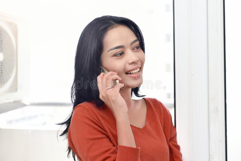 Mulher asiática de sorriso que faz uma chamada imagem de stock