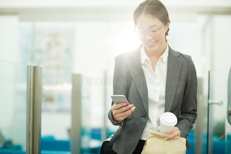 Mulher asiática de sorriso que sae do escritório fotos de stock royalty free