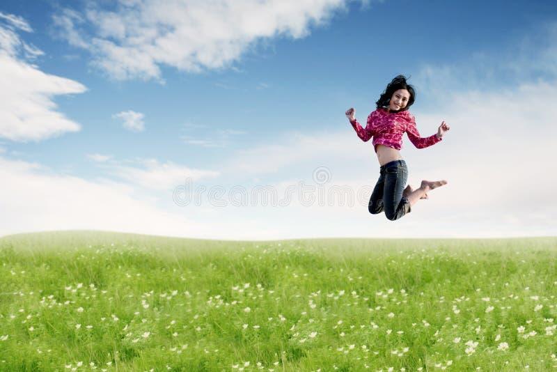 Mulher asiática despreocupada que faz um salto grande no prado foto de stock royalty free