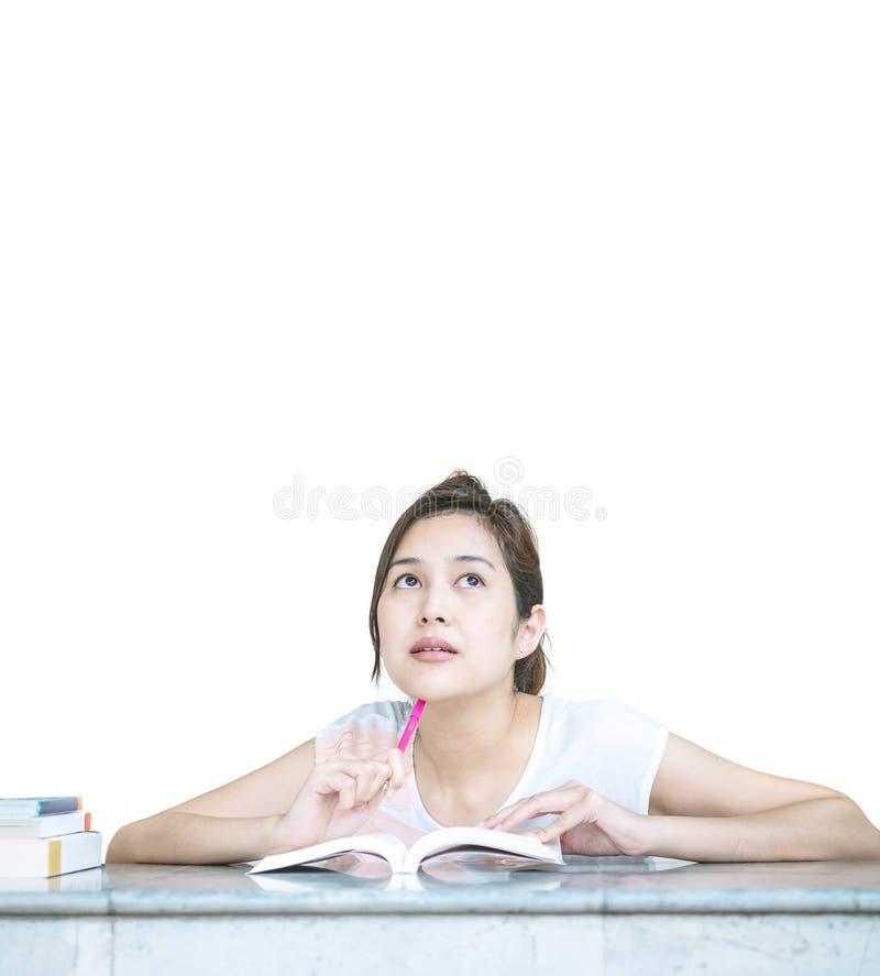 Mulher asiática do close up com cara de pensamento com um livro na tabela de mármore na frente da casa isolada no fundo branco foto de stock