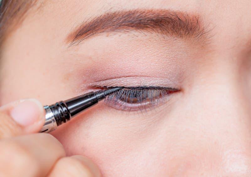 Mulher asiática do close up que aplica o lápis de olho no olho foto de stock