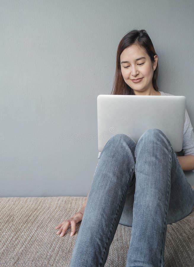 A mulher asiática do close up que senta-se para o caderno do computador do uso no conceito do trabalho na parede borrada do cimen fotos de stock