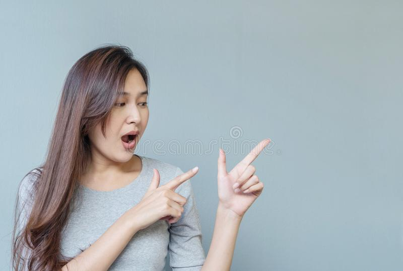 A mulher asiática do close up sustenta um dedo no ponto de duas mãos ao espaço com emoção entusiasmado da cara no backg textured  fotografia de stock