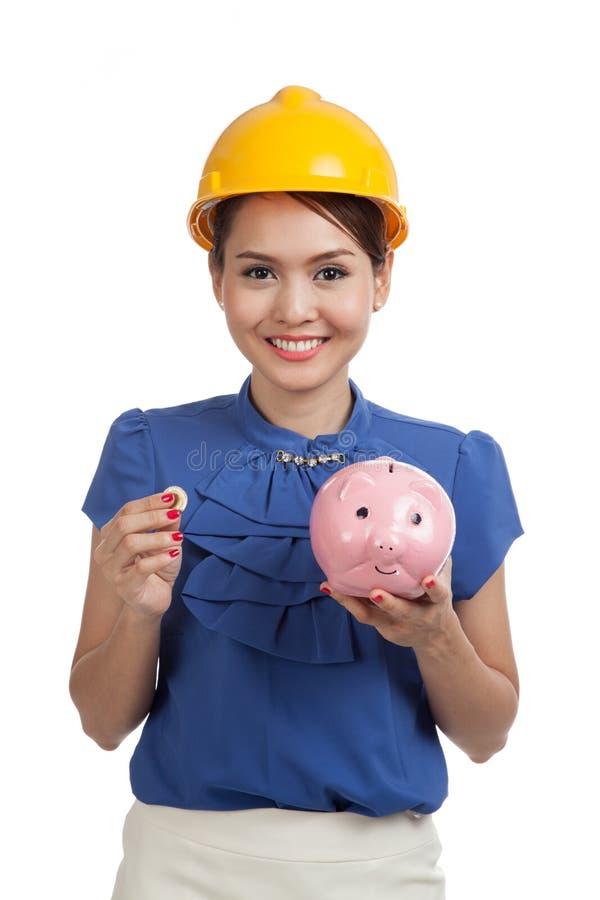 Mulher asiática do coordenador com uma moeda e um banco de moeda leitão foto de stock royalty free