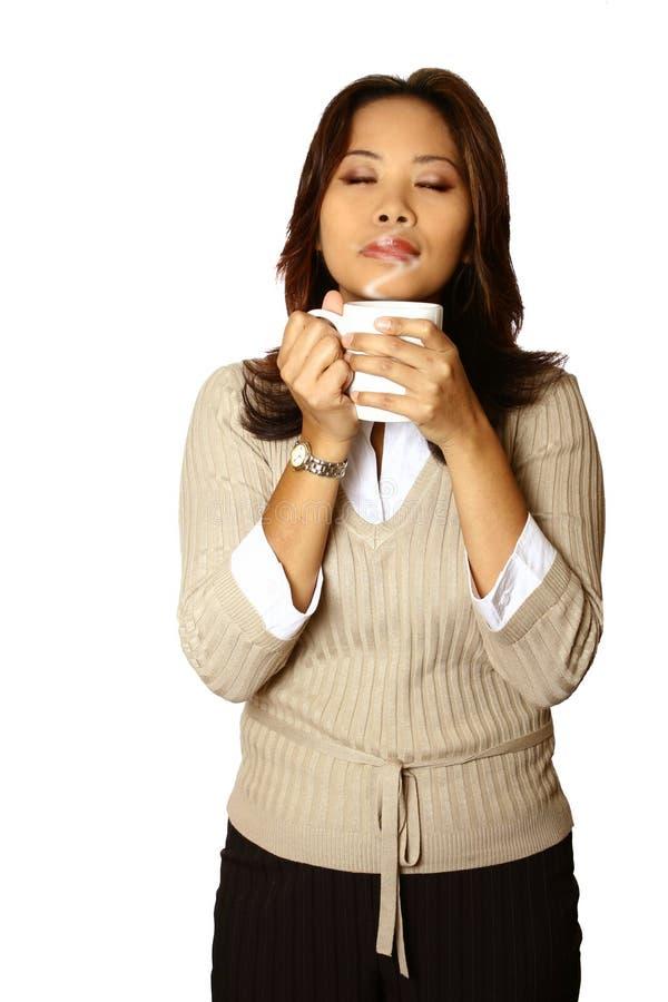 Mulher asiática do escritório que aprecia a chávena de café fotografia de stock royalty free