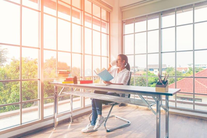 Mulher asiática do estilo de vida que bebe o café quente e o livro de leitura que sentam-se na tabela perto da janela, assim apre imagens de stock