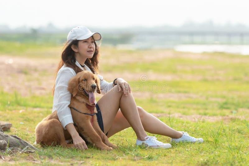 Mulher asiática do estilo de vida que joga com o cão da amizade do golden retriever tão feliz e para relaxar perto da estrada fotografia de stock