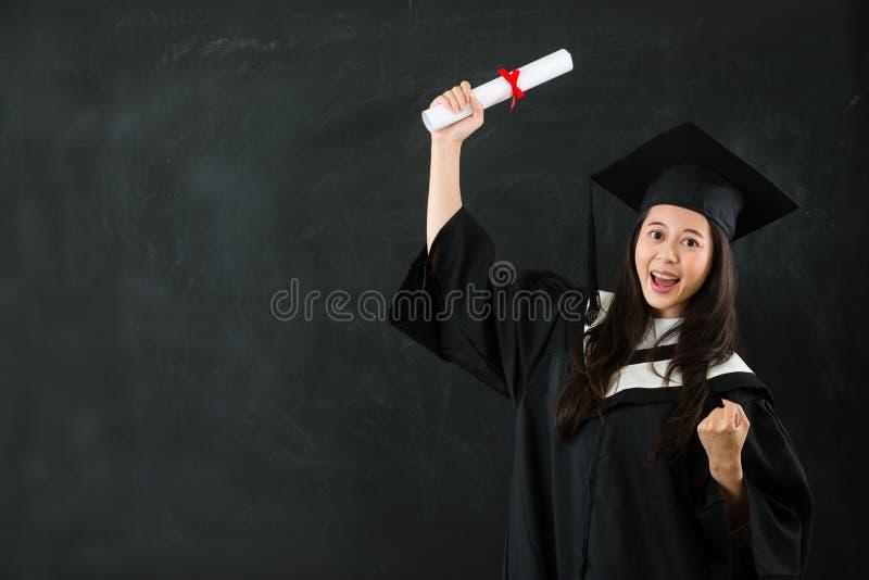 Mulher asiática do gesto que guarda o rolo da graduação fotos de stock royalty free
