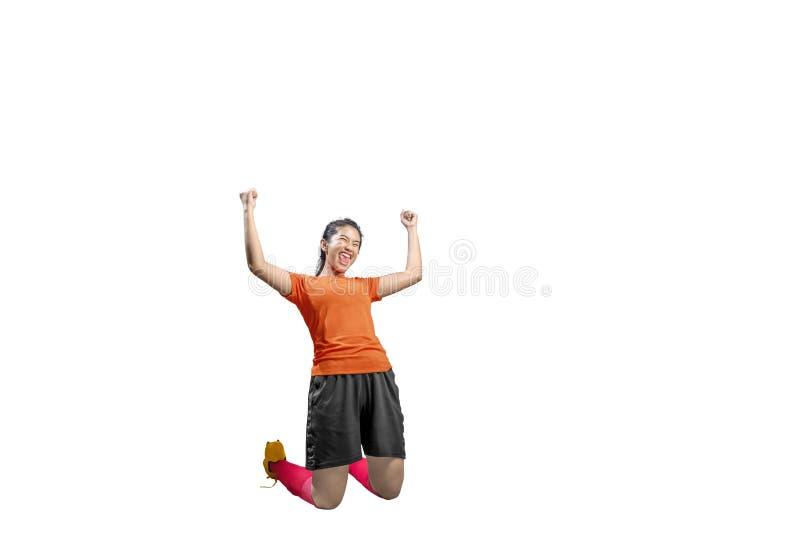 A mulher asiática do jogador de futebol comemora seu objetivo com braços aumentados e ajoelhamento fotos de stock