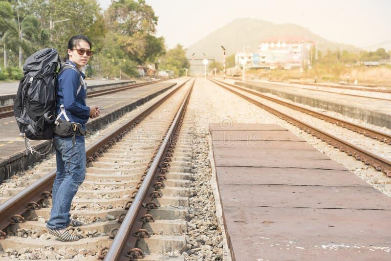 Mulher asiática do mochileiro no vestido ocasional e saco em, espera para o telefone celular esperto da posse da mão do trem da e imagens de stock