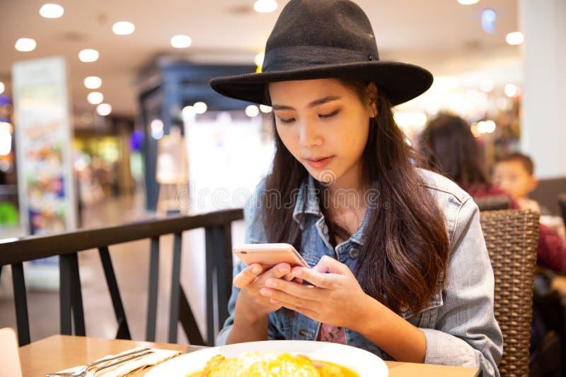Mulher asiática do moderno novo que veste um chapéu negro usando seu smartpho foto de stock