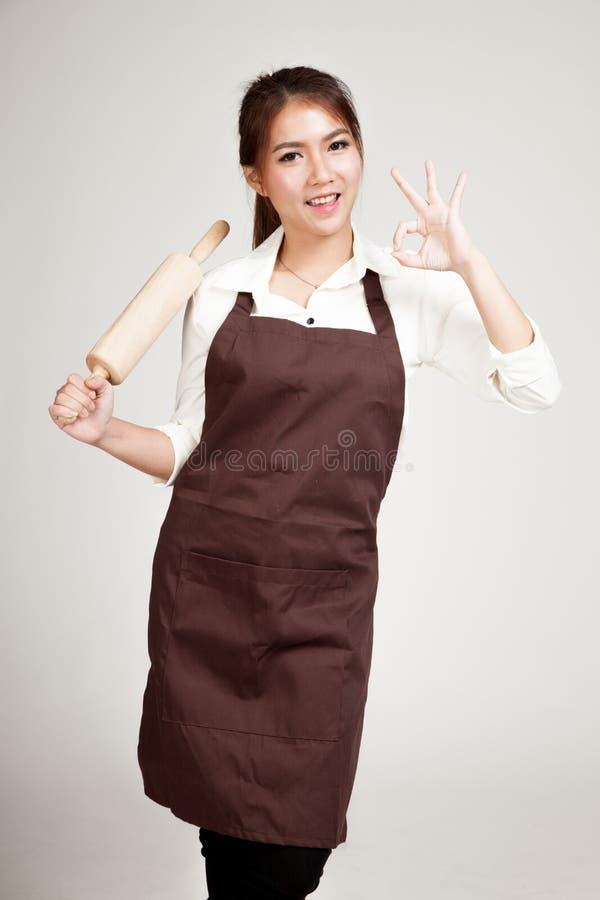 Mulher asiática do padeiro na APROVAÇÃO da mostra do avental com o pino do rolo de madeira fotos de stock royalty free
