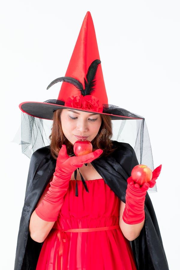 Mulher asiática do tiro do estúdio realizar vermelho da bruxa do traje na maçã no ha imagens de stock royalty free