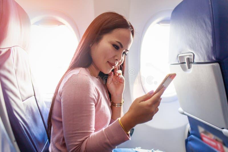 Mulher asiática do turista que senta-se perto da janela do avião no por do sol e que usa o telefone celular durante o voo foto de stock royalty free