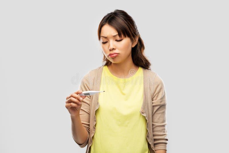 Mulher asiática doente com o termômetro que tem a febre fotografia de stock