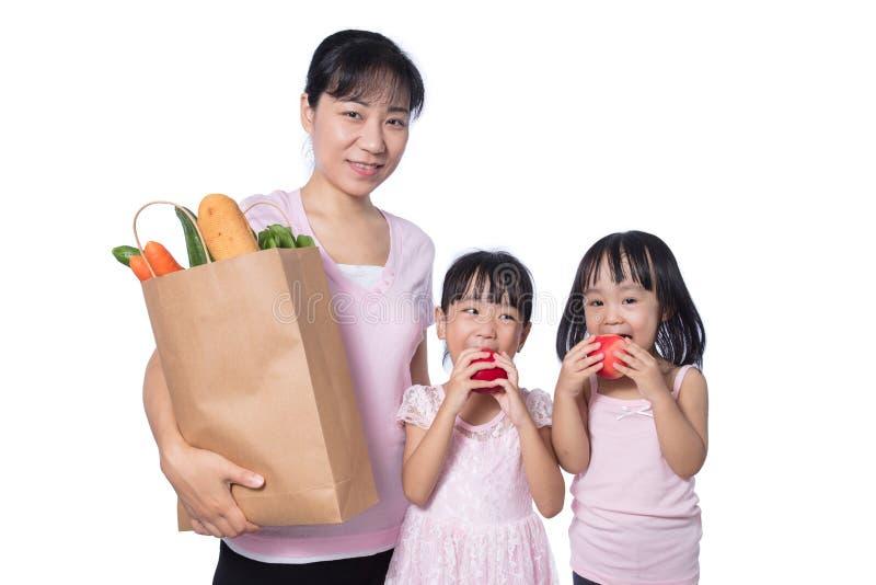 Mulher asiática e filhas que levam mantimentos fotos de stock