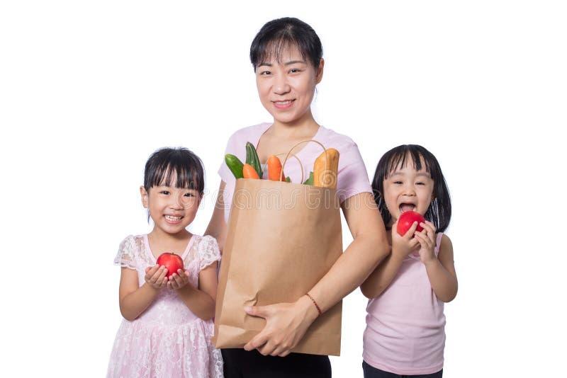 Mulher asiática e filhas que levam mantimentos fotografia de stock