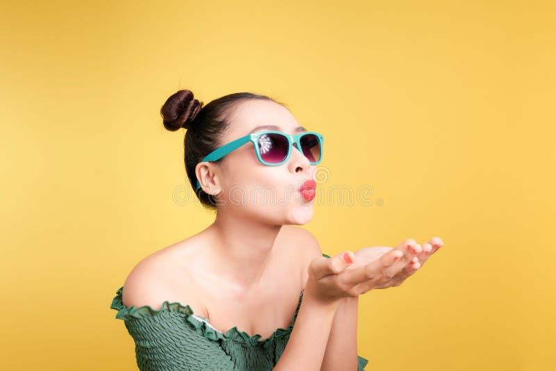 A mulher asiática elegante em óculos de sol na moda envia agains de um beijo foto de stock