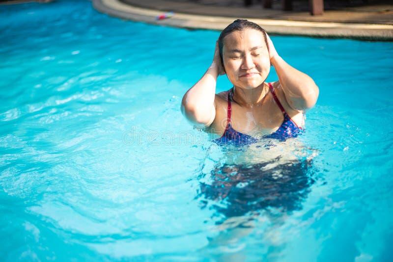 A mulher asiática em um biquini azul nada na associação imagens de stock