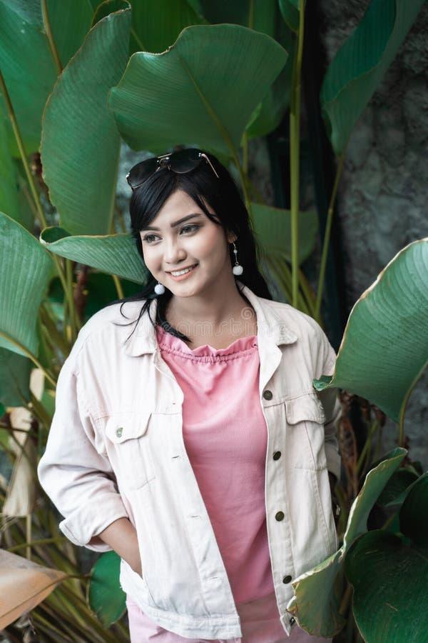 Mulher asiática entre as folhas verdes tropicais no verão fotografia de stock