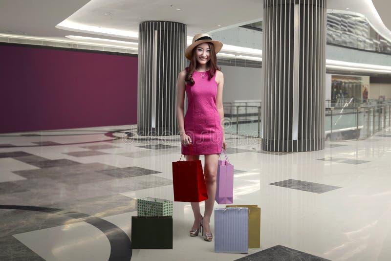 Mulher asiática entusiasmado feliz com o chapéu que guarda sacos de compras fotografia de stock royalty free
