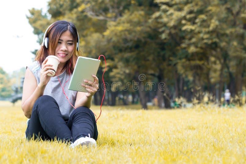A mulher asiática escuta a música na tabuleta e café guardar de vidro imagens de stock