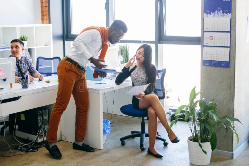 A mulher asiática está mostrando o original ao assistente africano ao falar no smartphone fotos de stock