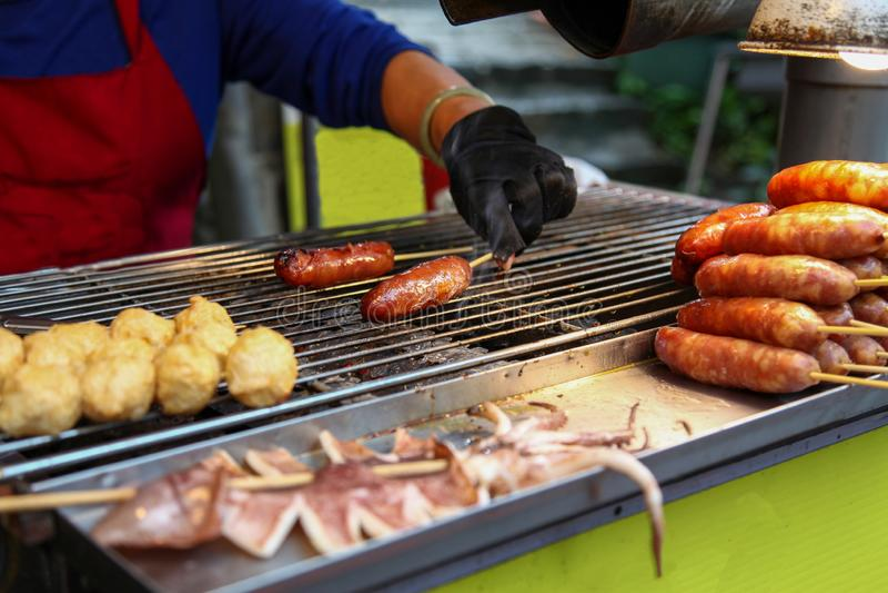 A mulher asiática está torcendo carne de porco Sausage tem fumaça para enchido de grelhador de Taiwan imagens de stock royalty free