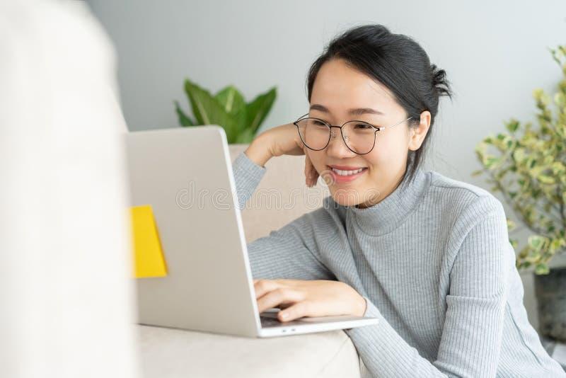 A mulher asiática está trabalhando em um portátil na casa Em sua cara é o sorriso quando trabalha no sofá imagem de stock royalty free