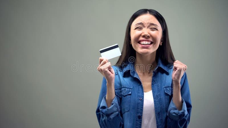 Mulher asiática extremamente feliz que guarda o cartão de crédito, baixa taxa de juro para creditar imagem de stock royalty free