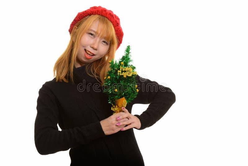 Mulher asiática feliz bonito que sorri ao guardar a árvore do ano novo feliz imagem de stock